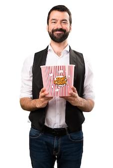 Koele mens die popcorns op geïsoleerde witte achtergrond eet