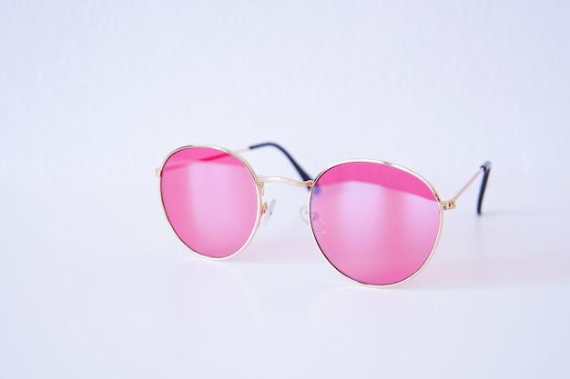 Koele moderne roze lichte geïsoleerde zonnebril. zomer reizen vakantie concept. uitverkoop kit. oogbescherming. selectieve aandacht