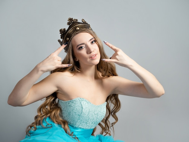 Koele prinses in een weelderige blauwe jurk en kroon maakt een rocker handgebaar, studiogrijze muur