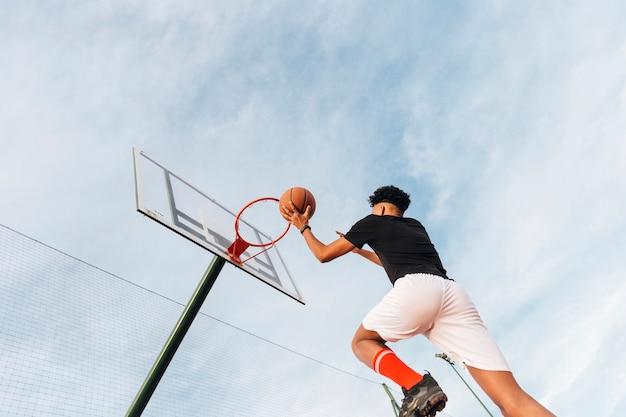 Koele sportieve mens die basketbal werpt in hoepel