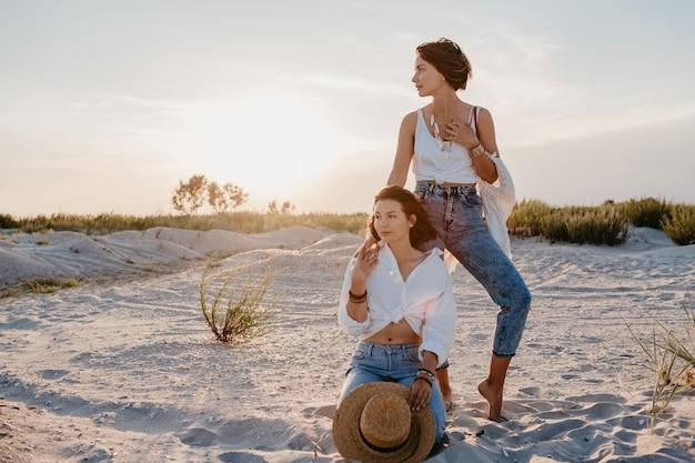 Koele twee jonge vrouwen die plezier hebben op het zonsondergangstrand, homo-lesbische liefdesromantiek