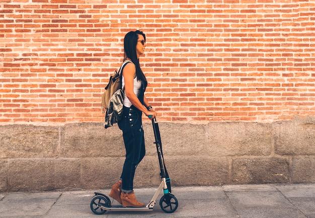 Koele vrouw die een elektrische autoped in de straat berijdt