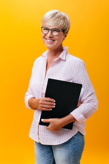 Koele vrouw in jeans, roze overhemd en bril vormt met papieren tablet op oranje achtergrond