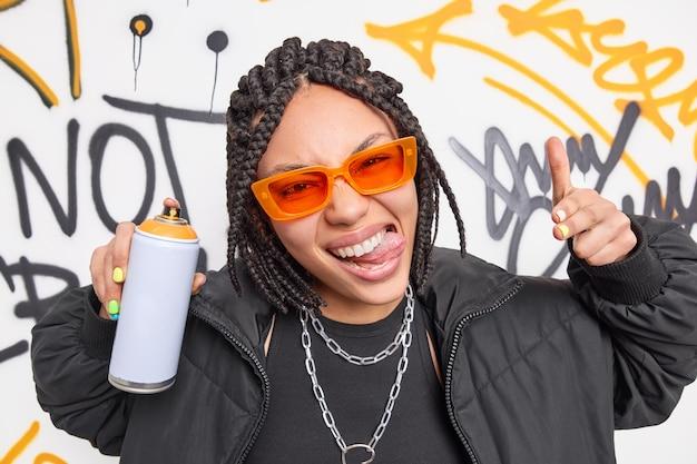 Koele vrouw steekt tong uit en maakt je gebaar, spuit verf uit spuitbus, creëert graffiti als straathooligan poseert tegen getekende muur
