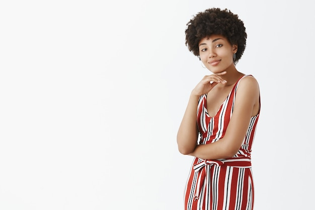 Koele, zelfverzekerde en aantrekkelijke afrikaanse vrouwelijke collega met een donkere huidskleur in een stijlvolle gestreepte overall, kin aanraken en grijnzend, hand op de borst kruisen, in zelfverzekerde pose over grijze muur staan