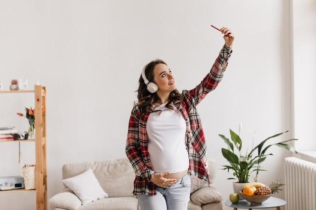 Koele zwangere vrouw in spijkerbroek en geruite overhemd raakt buik en luistert naar muziek in de koptelefoon