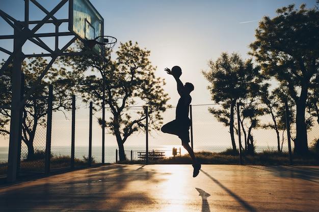 Koele zwarte man die sport doet, basketbal speelt bij zonsopgang, silhouet springt
