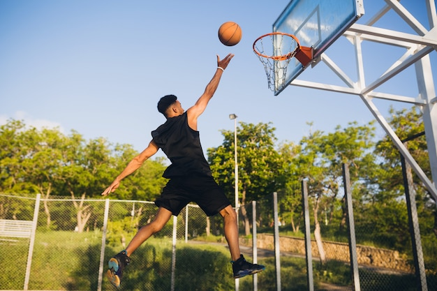 Koele zwarte man die sport doet, basketbal speelt bij zonsopgang, springt