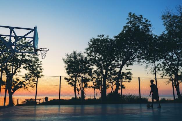 Koele zwarte man die sport doet, basketbal speelt op zonsopgang, silhouet