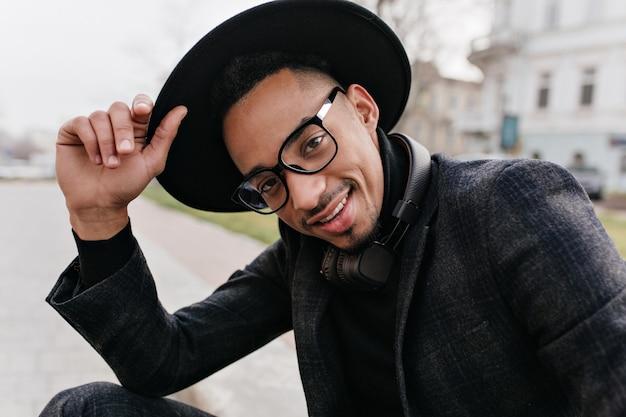 Koelende afrikaanse jongeman in glazen poseren met zelfverzekerde gezichtsuitdrukking. buiten schot van ontspannen man in hoed en wollen pak genieten van fotoshoot.