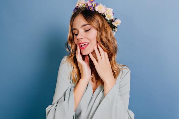 Koelende europese vrouw in bloemkrans poseren op blauwe muur