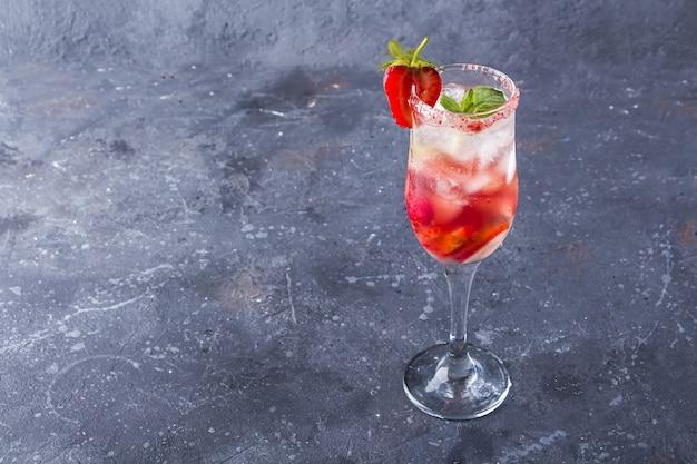 Koeling rossini italiaanse alcoholische cocktail met mousserende wijn, aardbei, ijsblokjes in champagne glas