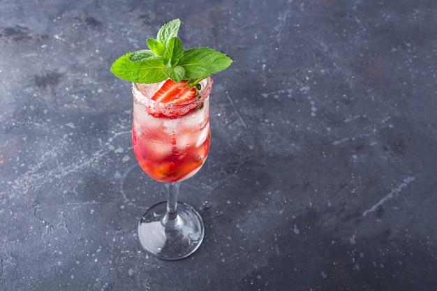 Koeling rossini italiaanse alcoholische cocktail met mousserende wijn, aardbei, ijsblokjes in champagne glas.