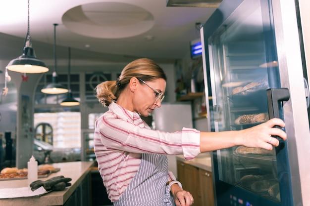 Koelkast met desserts. eigenaar van een franse bakkerij die een bril draagt en naar de koelkast met desserts kijkt voordat hij leveranciers belt
