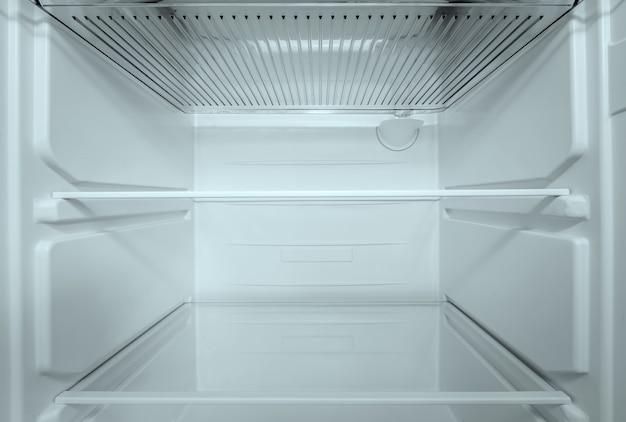 Koelkast open lege koelkast in interieur. close-up op lege koelkast met deur open. nieuwe schone koelkast