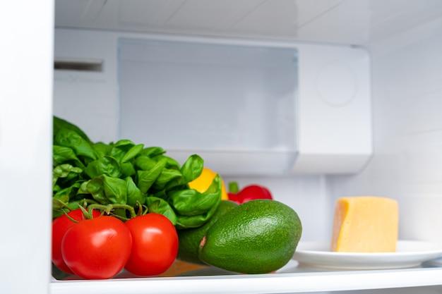 Koelkast plank vol met verse groenten close-up