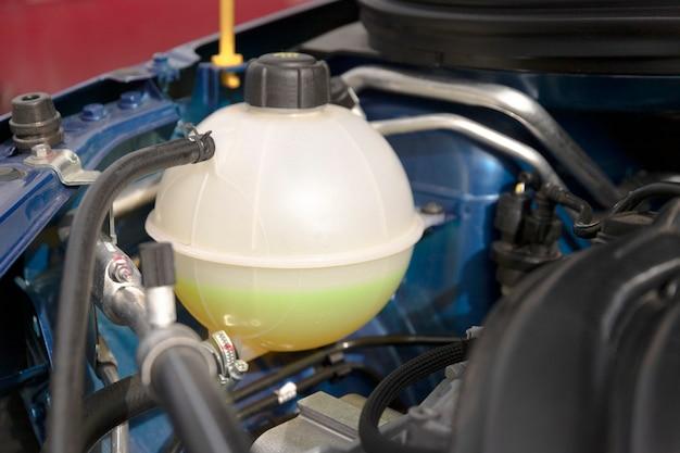 Koelvloeistoftank met antivries onder de motorkap van een nieuwe motor