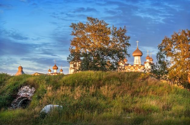 Koepels van de kerken op de solovetsky-eilanden van achter een heuvel in de stralen van de ondergaande zon