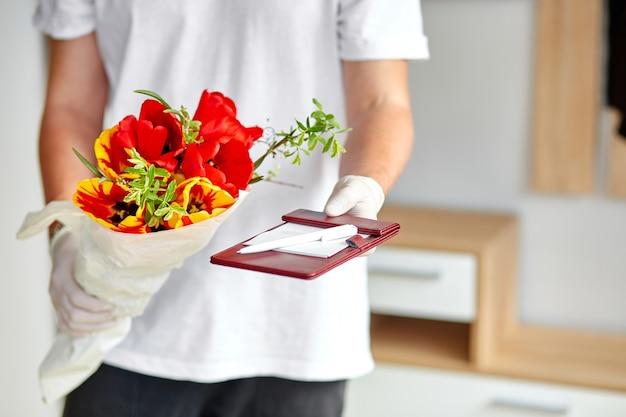 Koerier, bezorger in het wit in medische latexhandschoenen levert veilig online aankopen een boeket bloemen