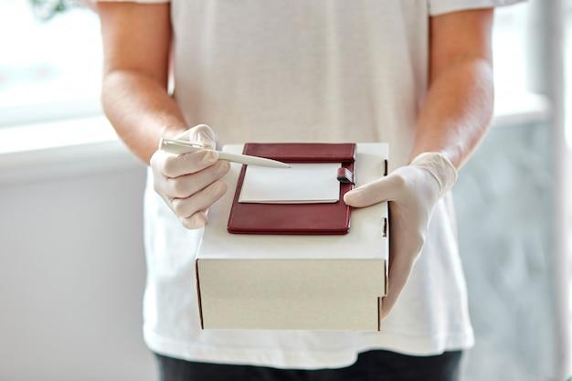 Koerier, bezorger in medische latex handschoenen levert veilig online aankopen tijdens de coronavirusepidemie.