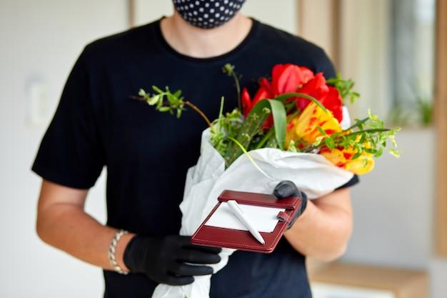 Koerier, bezorger in medische latex handschoenen levert veilig online aankopen van een boeket bloemen