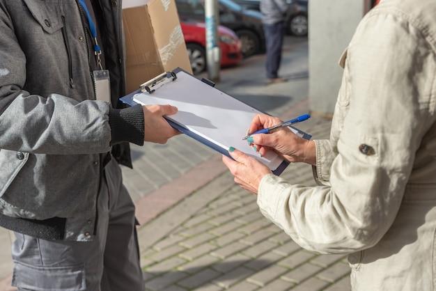 Koerier bezorgt bestelling aan vrouw die voor levering van pakket tekent, van dichtbij
