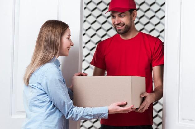 Koerier die de doos geeft aan de klant middelschot