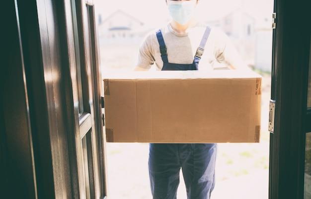 Koerier die doos levert terwijl hij latexhandschoenen en medisch masker draagt
