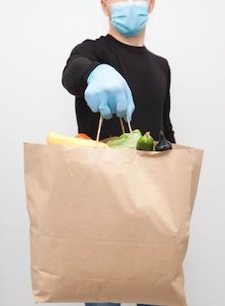 Koerier die gezichtsmasker en handschoenen draagt die een papieren zak houden