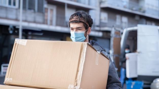 Koerier die op straat loopt, laadt een doos op zijn armen en een busje onscherp op de achtergrond