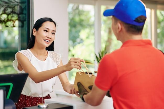 Koerier die verse zuivelproducten levert aan coffeeshop en pakket geeft aan glimlachende vrouwelijke eigenaar