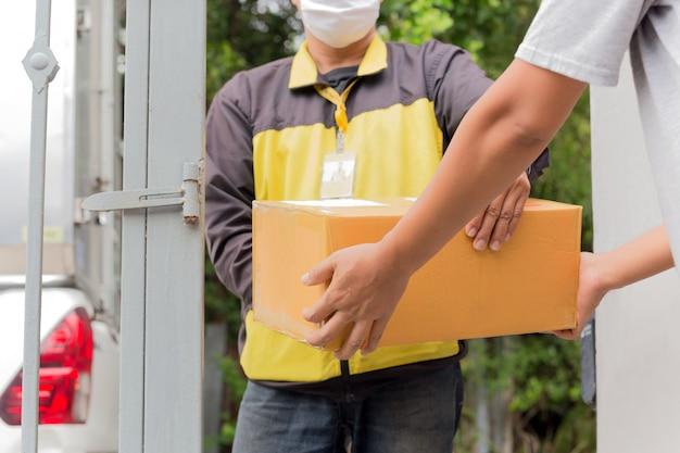 Koerier in beschermend masker bezorgt pakketklant thuis onder quarantaine, coronavirusuitbraak.