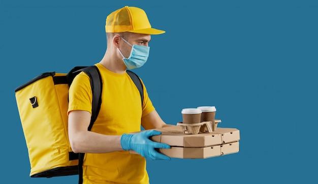 Koerier in beschermend masker en medische handschoenen bezorgt afhaalmaaltijden en koffie. bezorgservice onder quarantaine. kopieer ruimte voor tekst