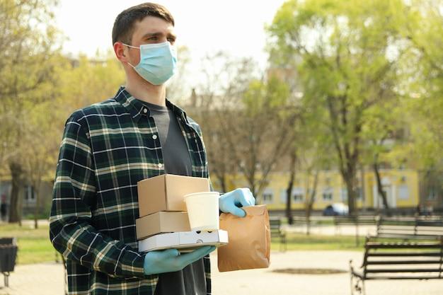 Koerier in beschermend masker en medische handschoenen bezorgt afhaalmaaltijden