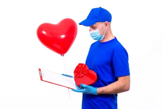 Koerier in beschermend masker, handschoenen houdt rode hartvormige geschenkdoos en ballon voor valentijnsdag