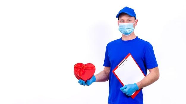 Koerier in beschermend masker, handschoenen houdt rode hartvormige geschenkdoos voor valentijnsdag.