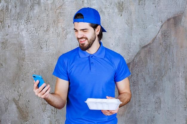 Koerier in blauw uniform met een plastic afhaaldoos en nieuwe bestellingen via de telefoon.