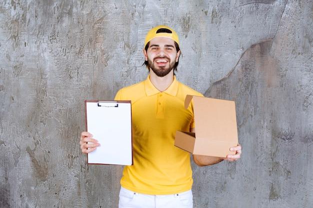 Koerier in geel uniform die een open kartonnen doos vasthoudt en om een handtekening vraagt