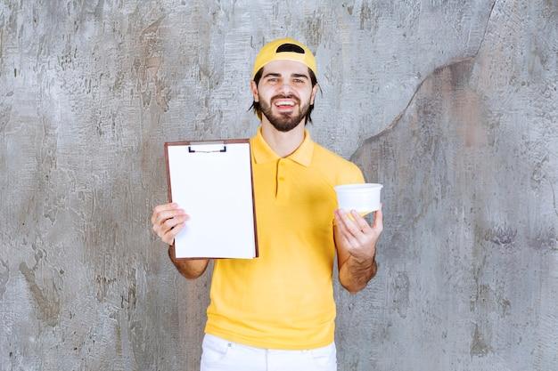 Koerier in geel uniform die een plastic beker vasthoudt en om een handtekening vraagt.