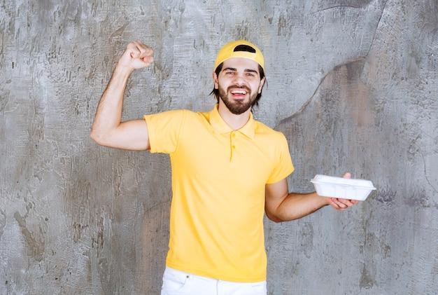 Koerier in geel uniform levert een plastic afhaaldoos en toont een positief handteken.