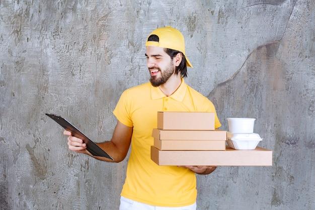 Koerier in geel uniform met afhaalpakketten en boodschappentas en het controleren van de klantenlijst.