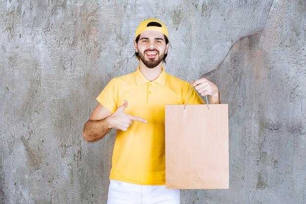 Koerier in geel uniform met een kartonnen boodschappentas.