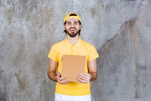 Koerier in geel uniform met een open kartonnen doos