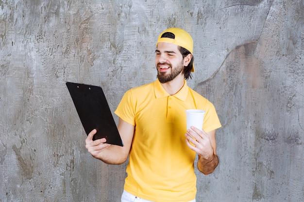 Koerier in geel uniform met een wegwerpbeker en het lezen van de klantenlijst
