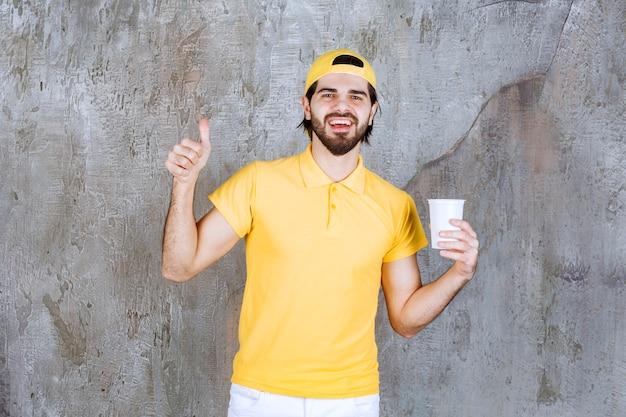 Koerier in geel uniform met een wegwerpbeker en positief handteken.