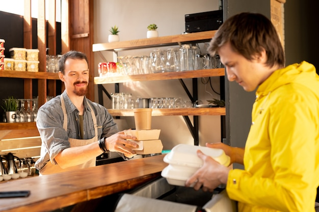 Koerier in gele jas lunchdozen aanbrengend thermische zak terwijl ober stapel voedsel dozen aan hem in café doorgeeft