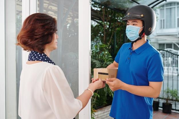 Koerier in helm en medisch masker die kartonnen doos naar senior vrouw brengt en betaling met creditcard accepteert
