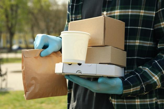 Koerier in medische handschoenen bezorgt afhaalmaaltijden