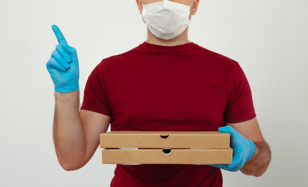 Koerier in medische handschoenen en masker houdt pizzadozen. pizza bezorging tijdens de quarantaine. service quarantaine pandemie coronavirus virus griep 2019-ncov concept.