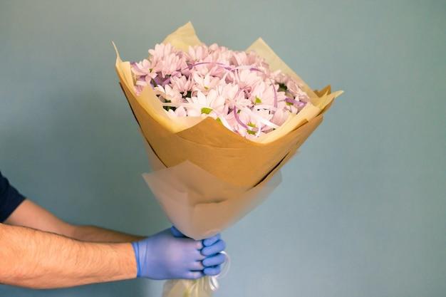 Koerier in medische handschoenen en masker levert chrysanten. contactloos bloemen bezorgen. quarantaine. coronavirus.